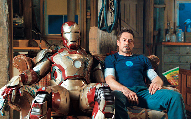 Tony Stark sitting next to his Iron Man suit.